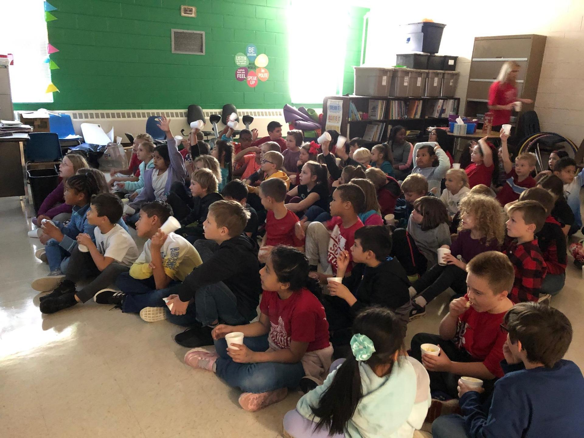 Students enjoy watching a movie and eating popcorn