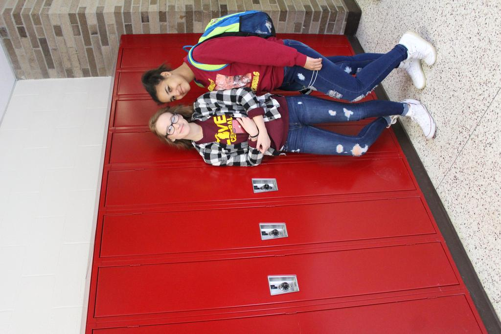 Two smiling students standing in front of lockers