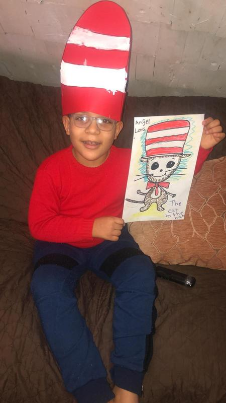 Angel wearing makeshift Cat in the Hat hat and holding drawing