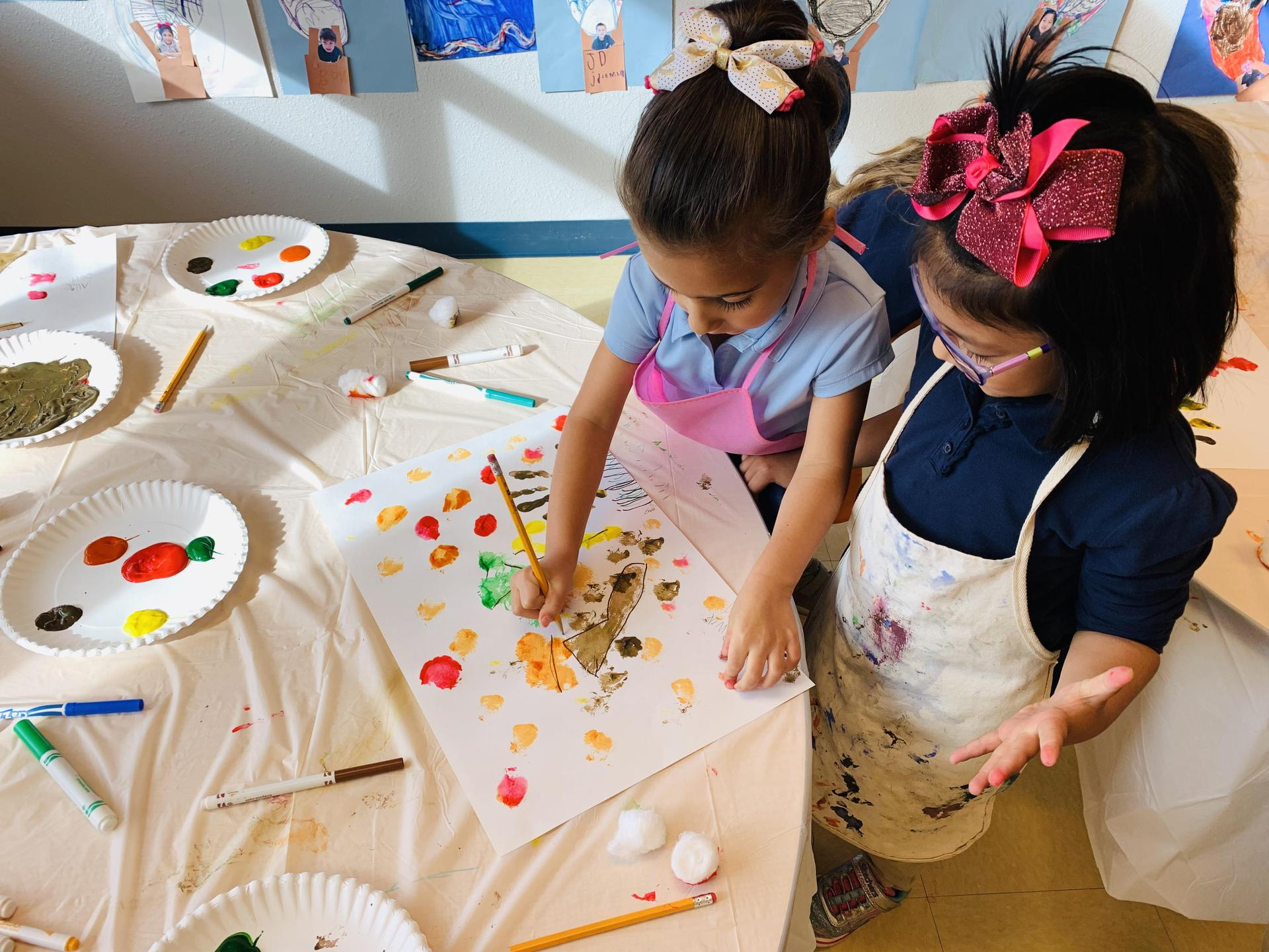 Two girls paint together.