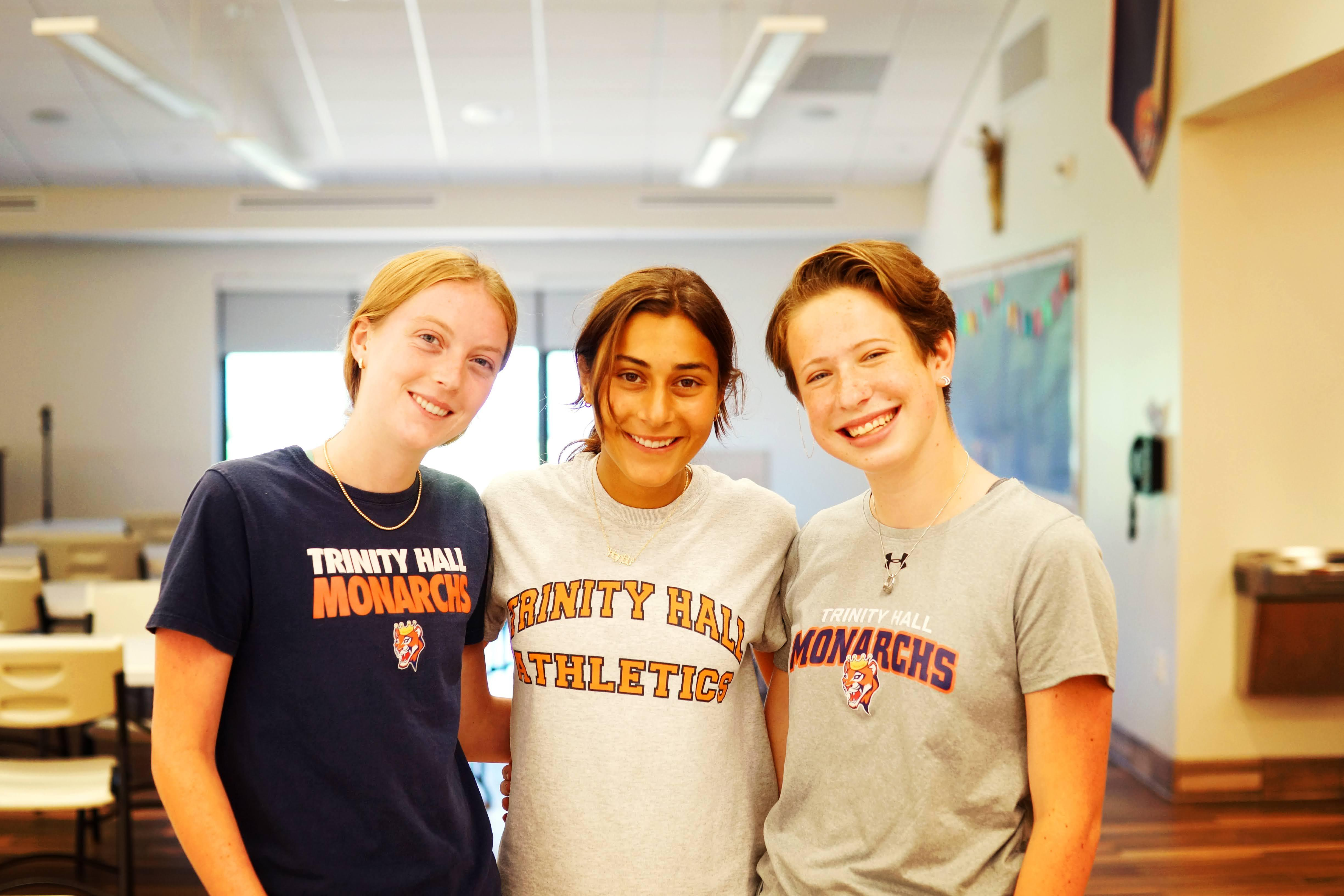 three trinity hall students smiling for the camera