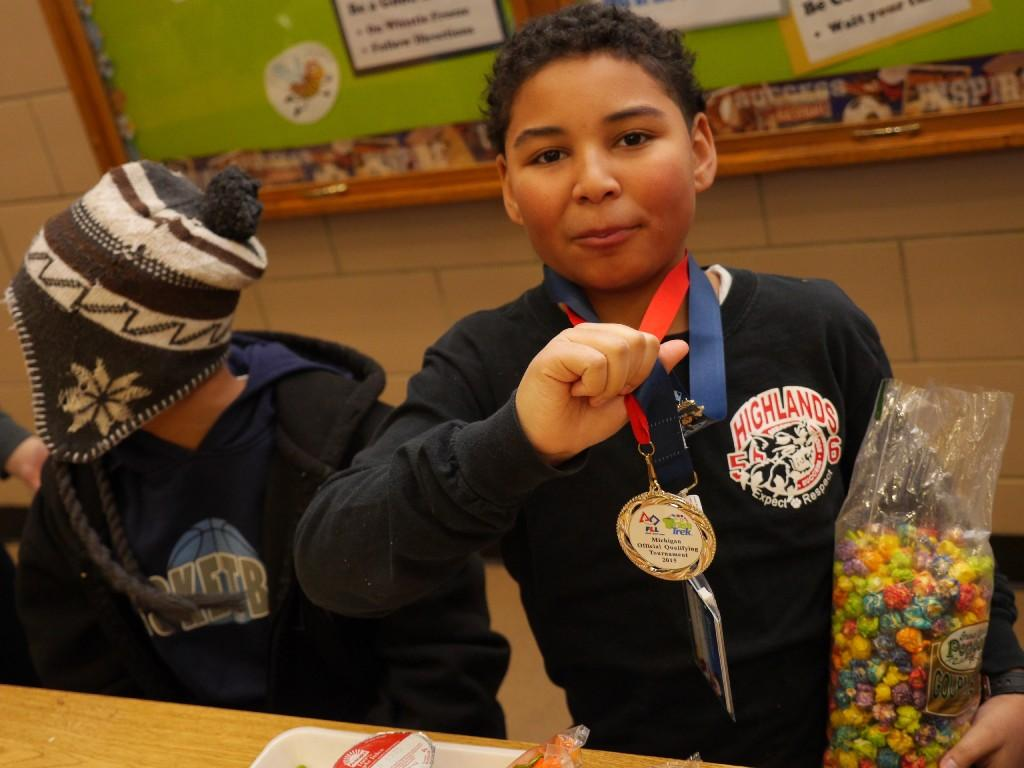 students eating lunch in lunchroom while showing off medals