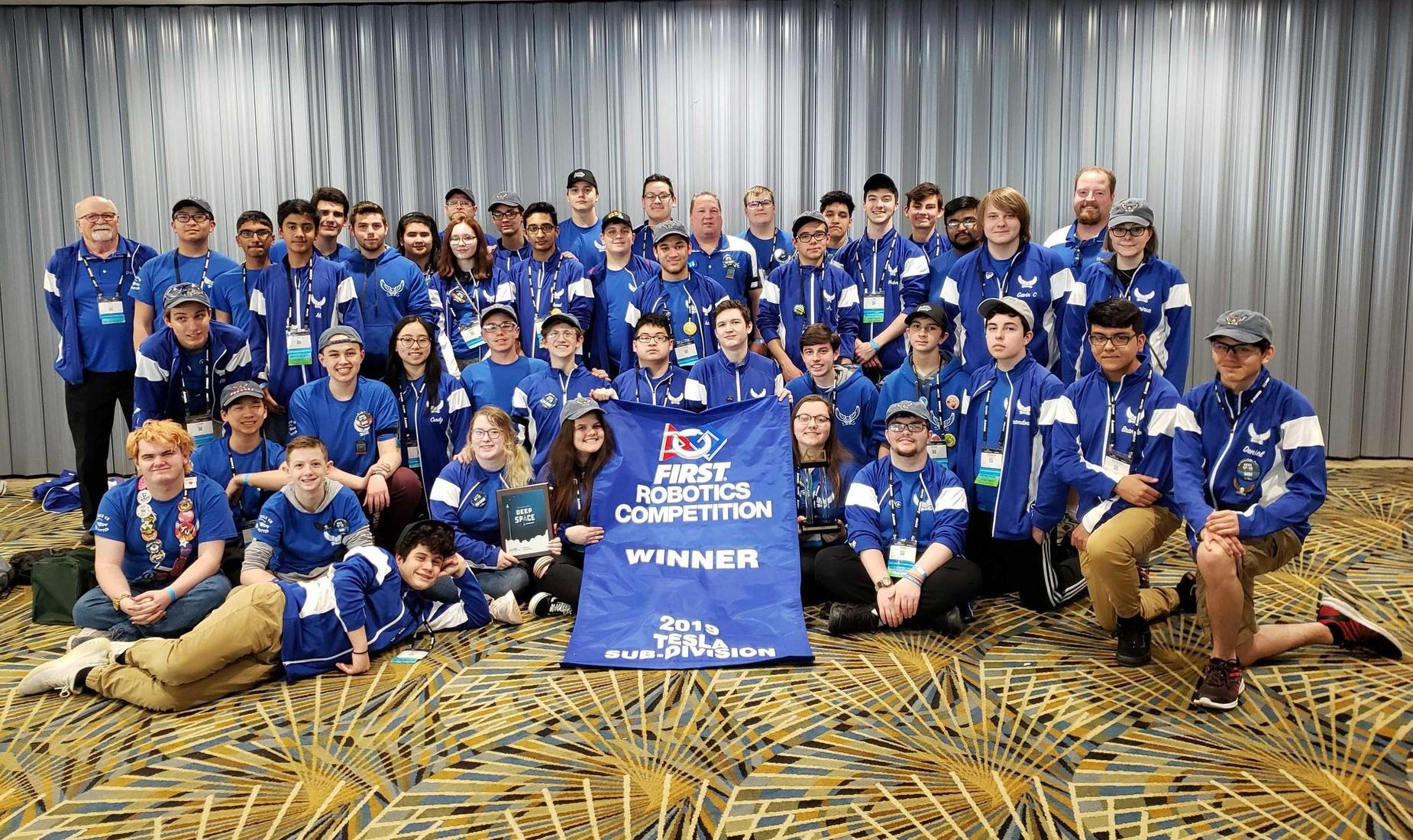 BHS Robotics Team at FIRST Robotics World Championships. They are wearing blue t-shirts and holding a winning banner.