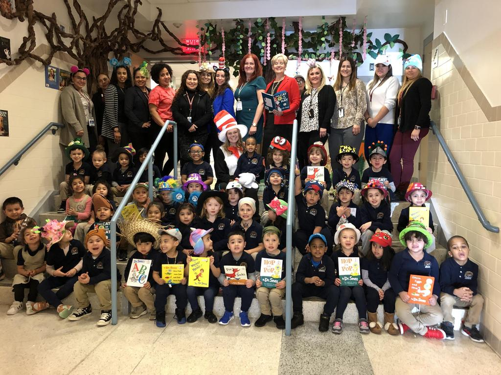 group photo of kindergartners with teachers, aides, and Hudson Administration in the front entryway of the school