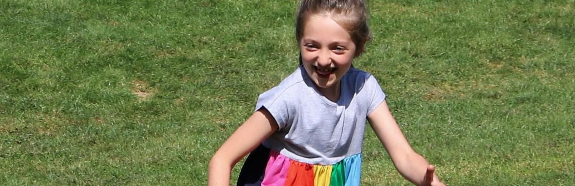 Photo of student running and smiling during recess
