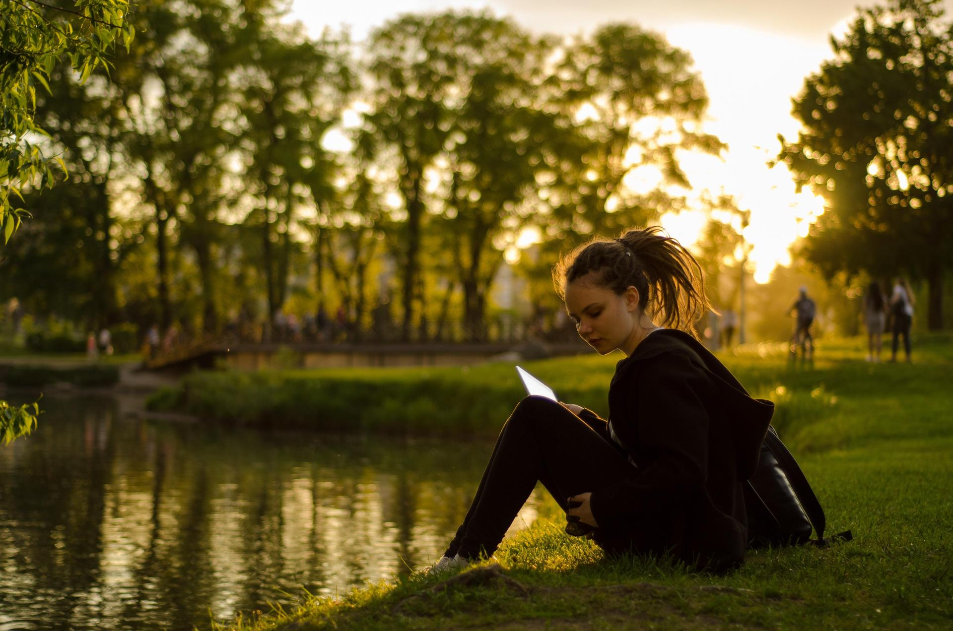 Girl reading by a pond