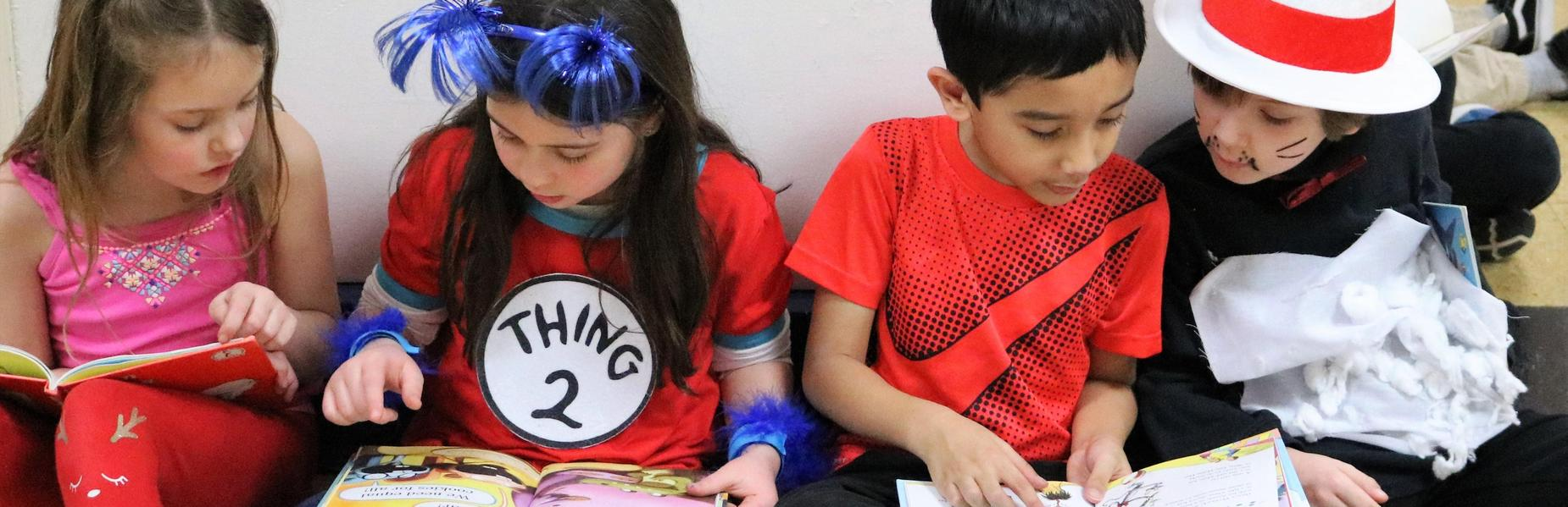 Photo of four 2nd graders, two wearing Dr. Seuss-inspired gear as all four read their favorite Seuss books together for Read Across America Day.