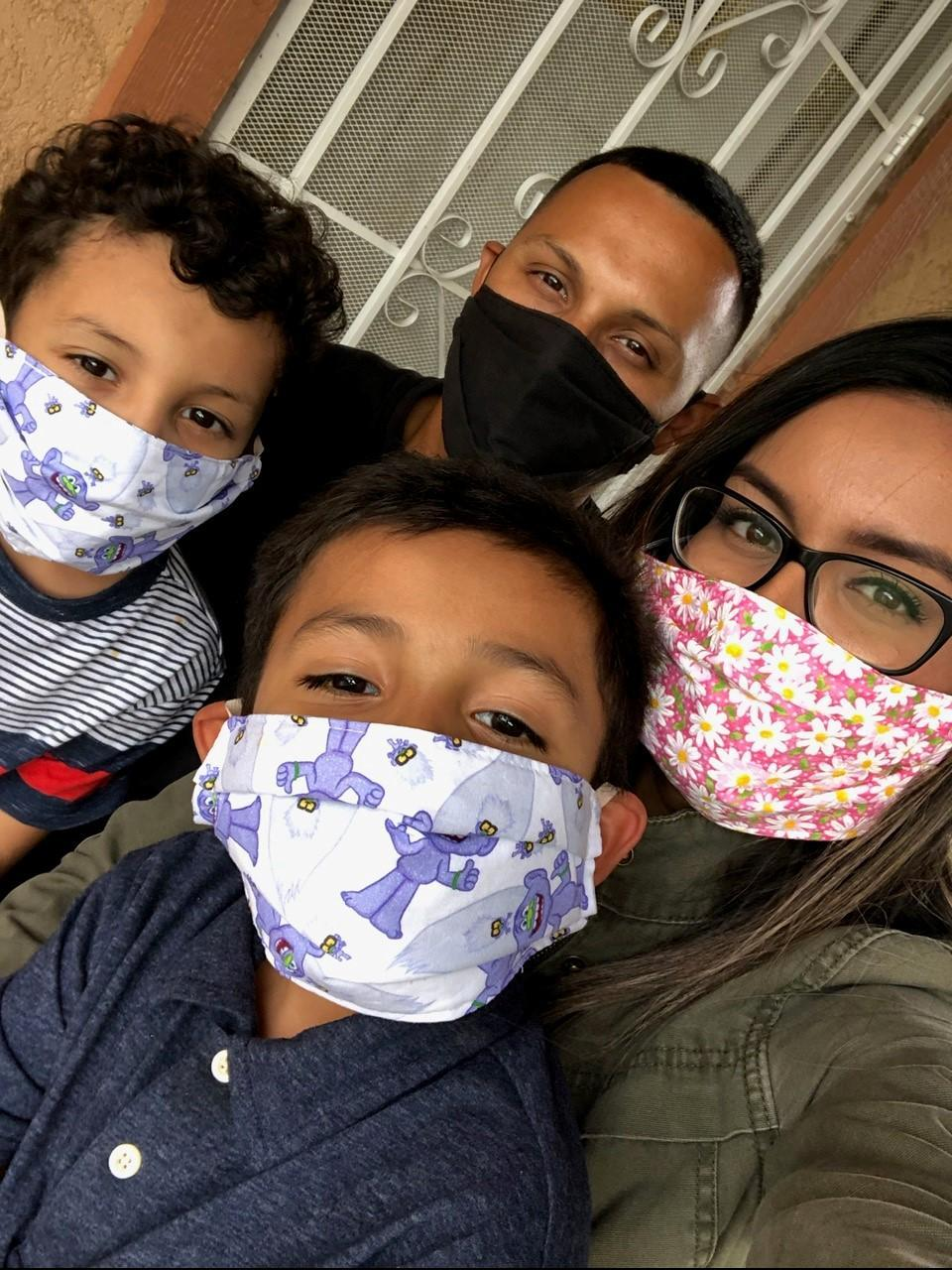 Family of four wearing masks posing for picture