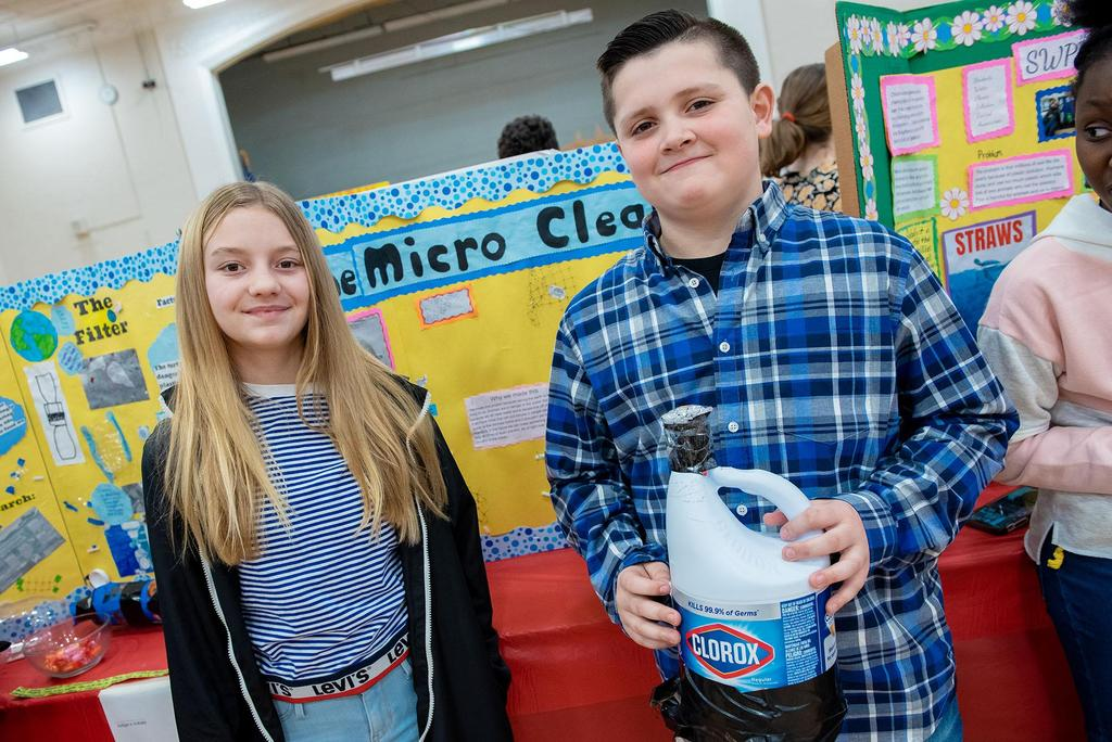 Two students, one holding a device made out of a container of bleach