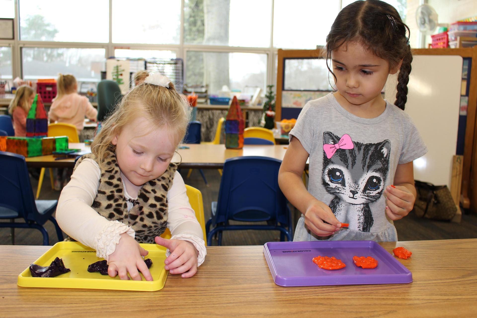 two girls play with preschool clay