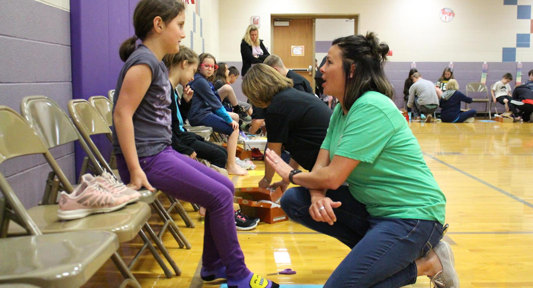 Female Sucess Liaison takes a knee to help a young female student try on shoes at a school shoe drive