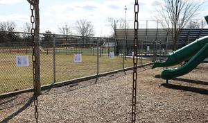 Wide shot of playground with Storywalk pages on fence.