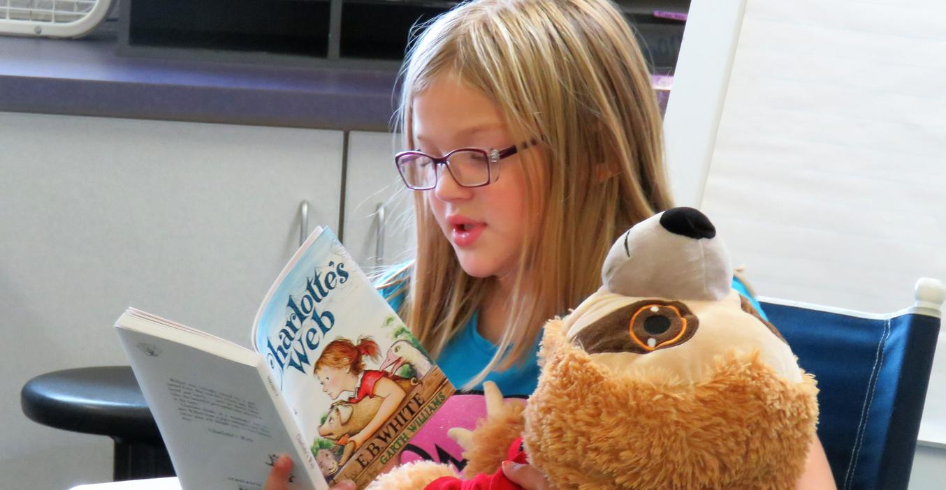 A student enjoys reading Charlotte's Web.