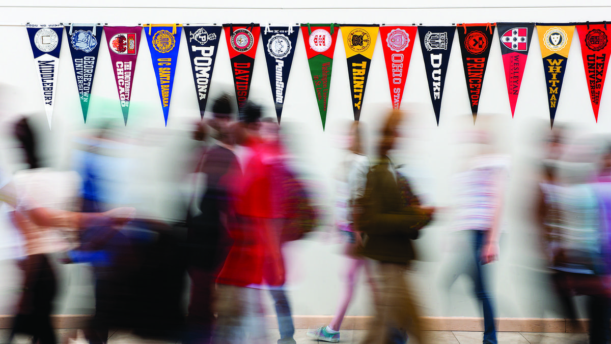 College pennants in hallway with students