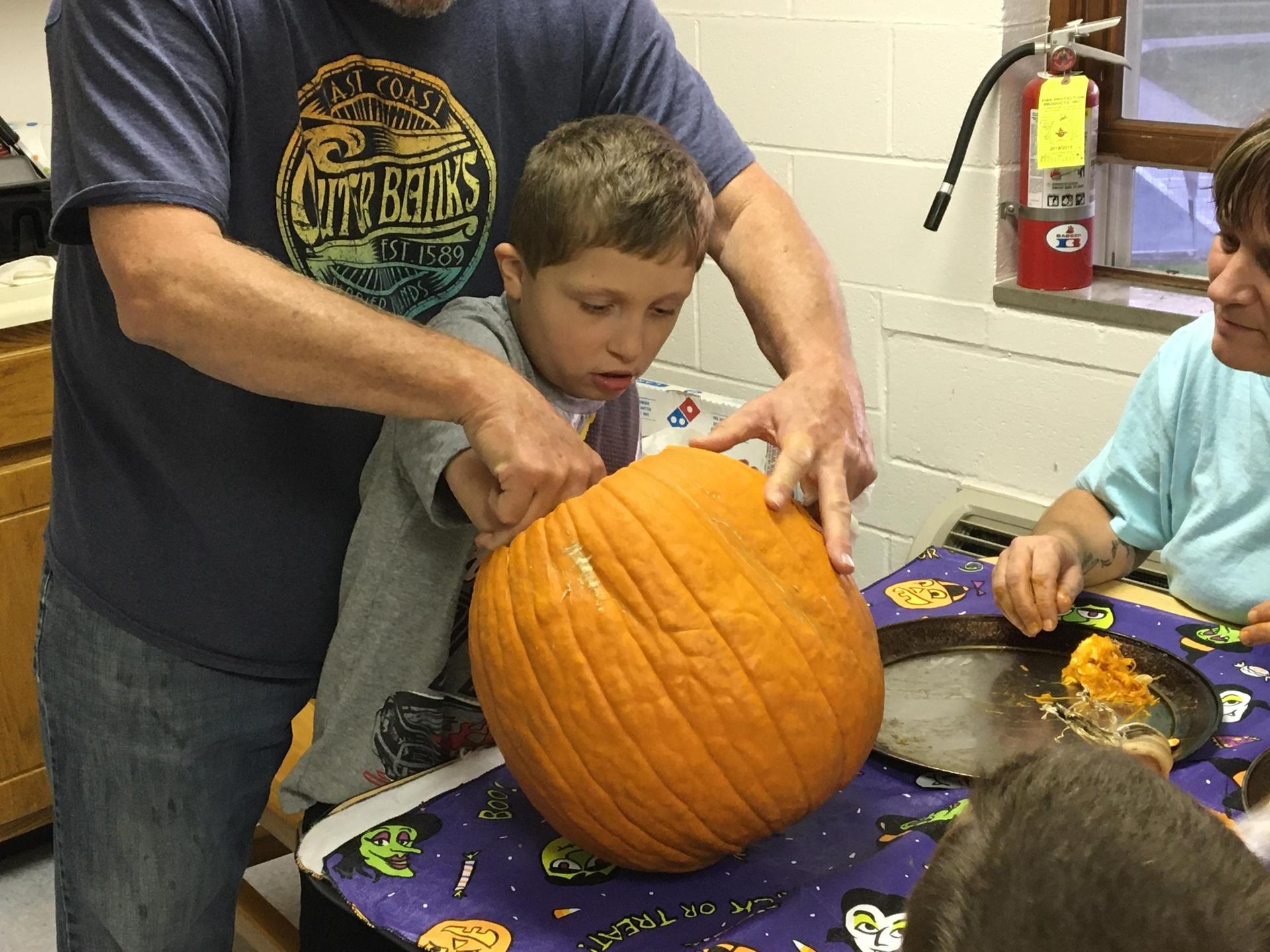 Student digging into a pumkin to clean out the seed with RCS standing close behind