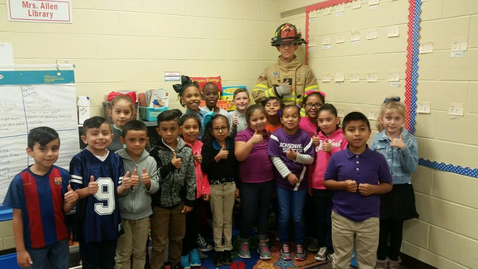 2nd grade students posing with a local fireman