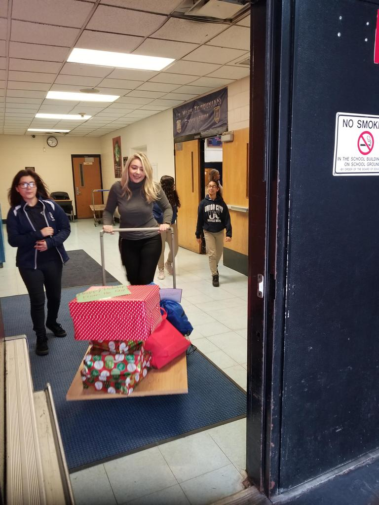 ms velazquez pushing a cart with winter clothes for the PERCC shelter