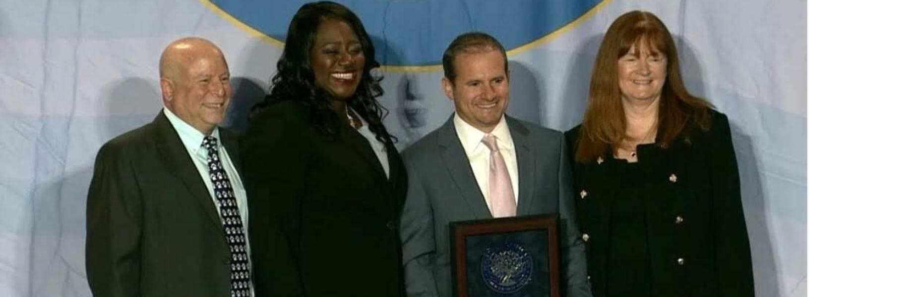 Photo of Dr Dolan, Dr Perry & Washington School teacher posing with National Blue Ribbon Schools program director during ceremony.