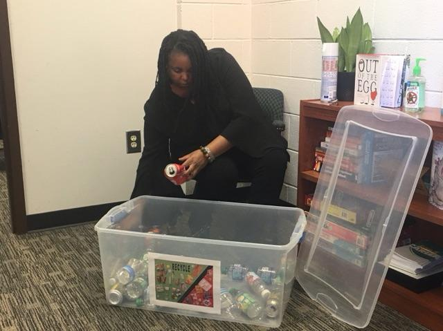 """""""GOA Recycles"""". Ms. Gratic sorting soda cans."""