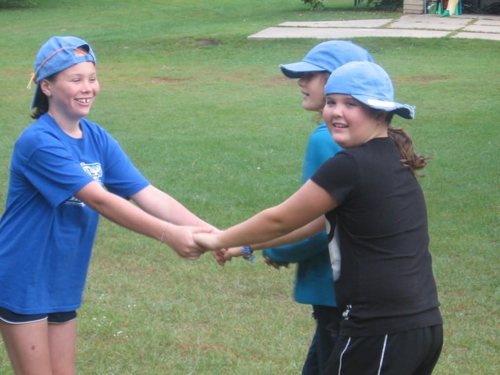 three students join hands for game outside