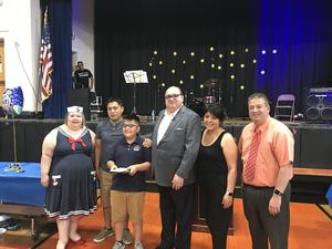 Fathers Day Scholarship winner with family and principal