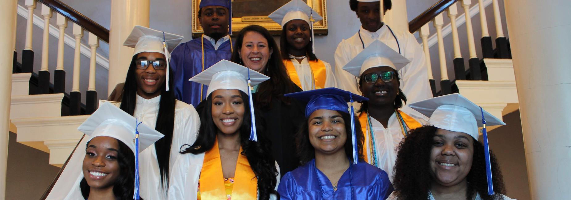 Students stand with a teacher at their graduation.