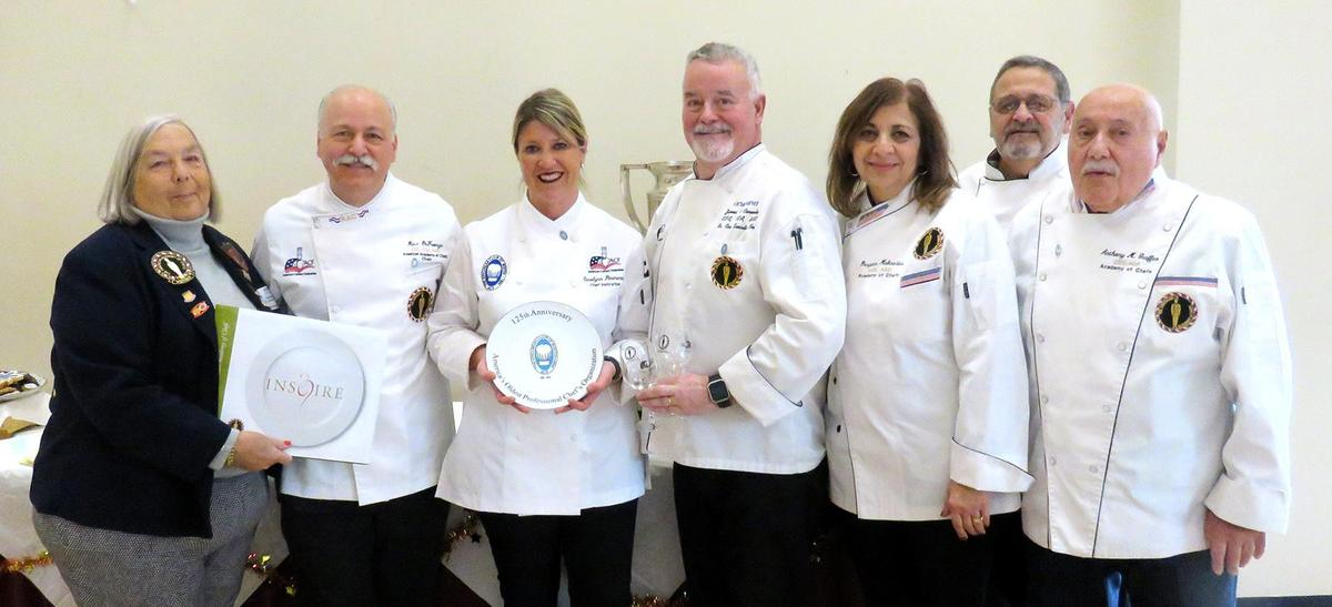 Chefs from the Epicurean Club of Boston present a book to Culinary Arts Director Carolynn Parmenter