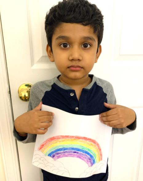 Boy holding rainbow drawing