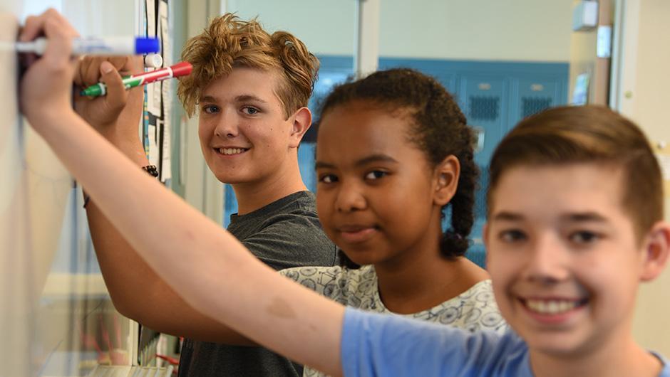 Three math students at whiteboard