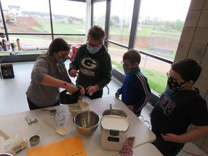 Art teacher Kathy Bailey helps students use the hand mixer.