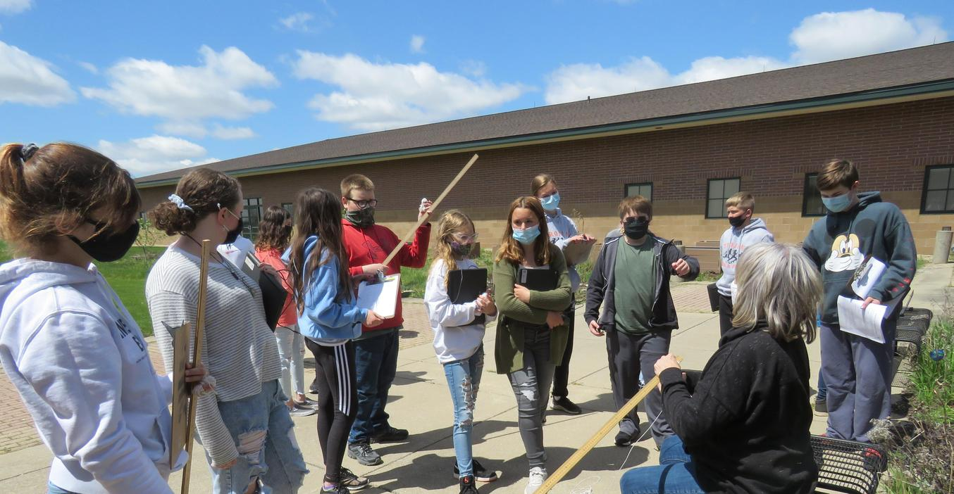 TKMS science students get instructions for an outdoor experiment from teacher Jamie Bowman.