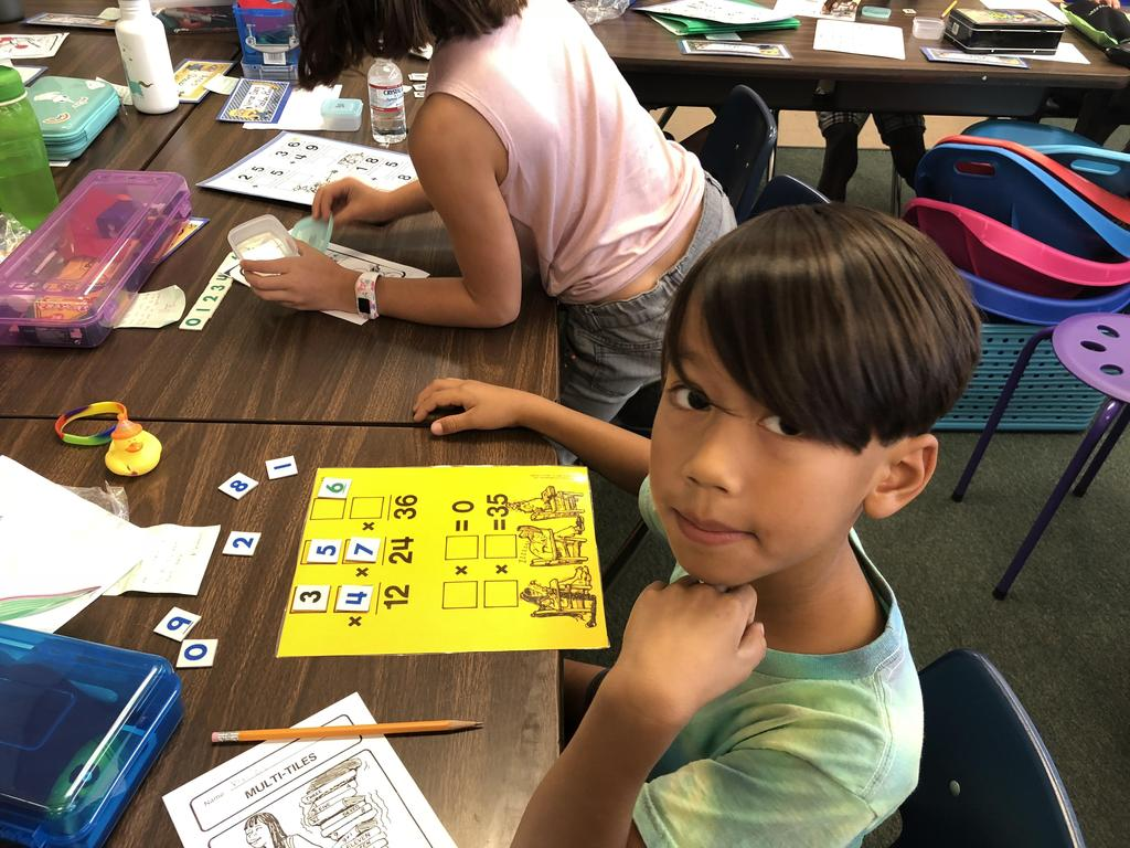 A boy is working on math through math tile cards.