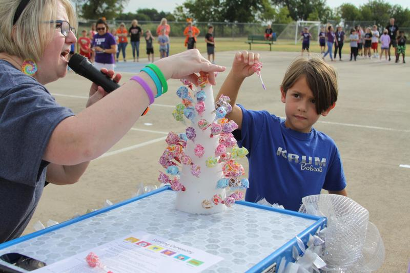 boy student in a blue shirt selects a lollipop from the lollipop tower