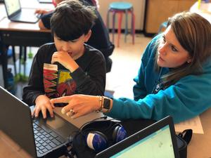 Student and teacher complete coding activity together