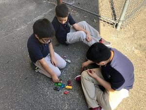 three boys playing with toy cars