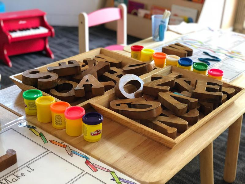 A desk in a classroom with play dough and wooden letters on it in a tray.