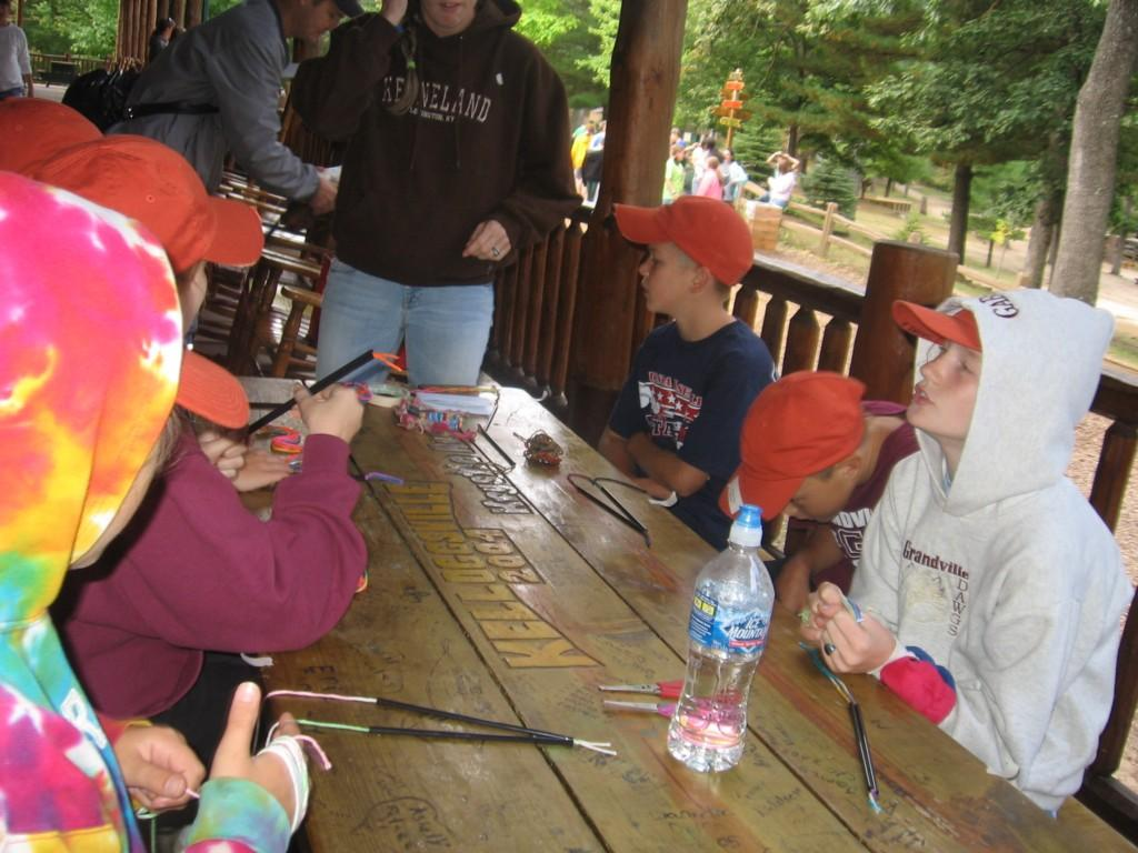 students make yarn craft on porch of cabin