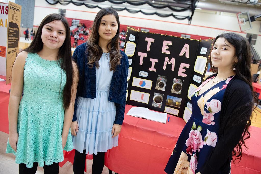 Three female students in front of their project, Tea Time