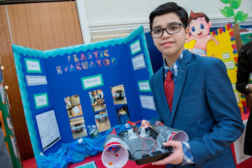 A student holds his handmade device called the Plastic Evacuator