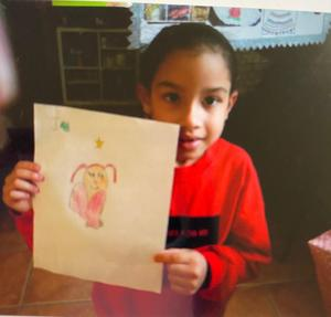Student holding drawing of girl with heart