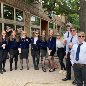 group of teens pose in matching uniforms outside restaurant
