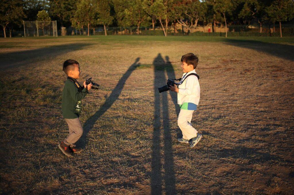 The children are exploring shadows capturing pictures with the camera.