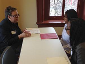 Woman sitting at a table speaking to two students.