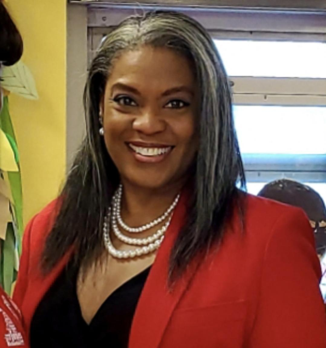 principal belton smiling in a red blazer jacket and pearls