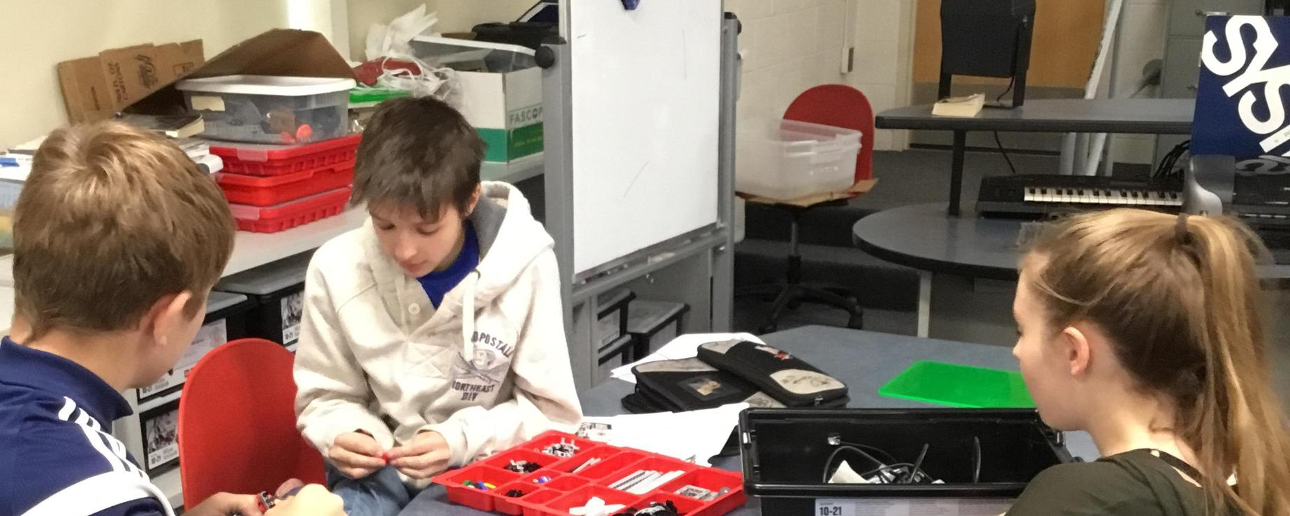 Three Robotics club members comparing tools to use to build a robot