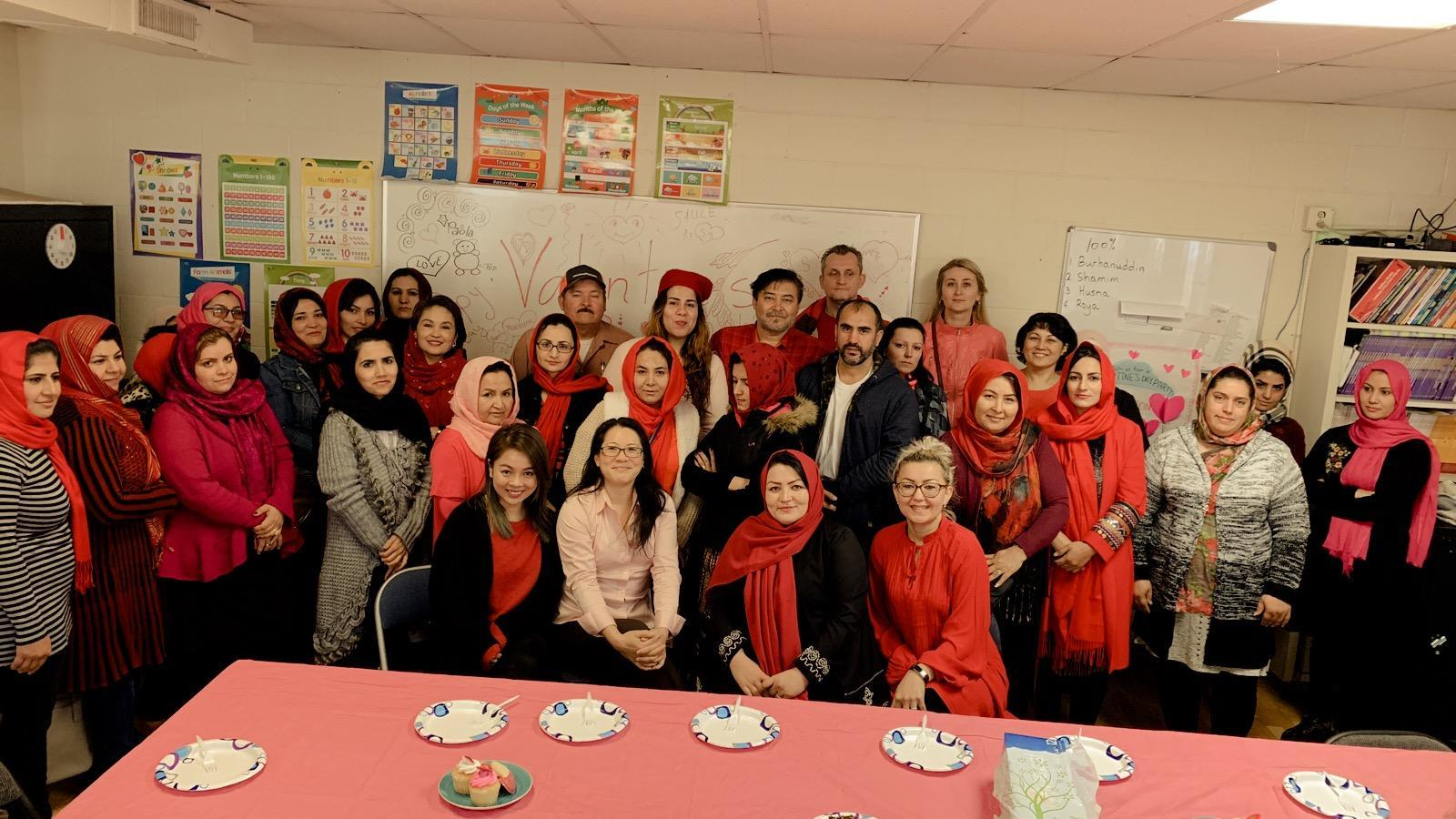 Group picture of students and staff dressed in red and pink for a Valentine's Day party.