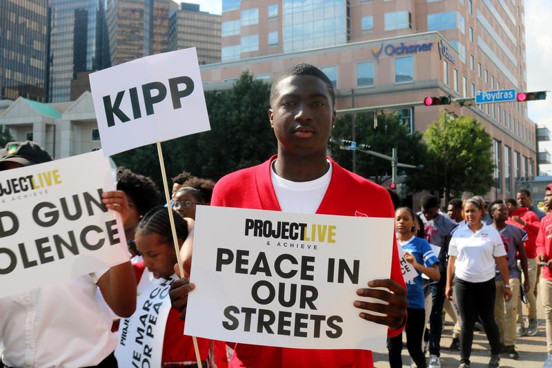 A male KBTW student holds a protest sign as he marching in the street