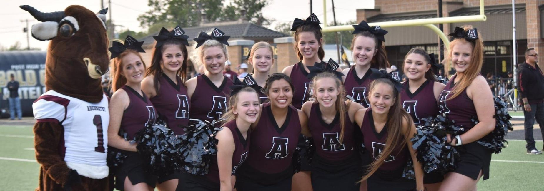 Cheerleaders pose with mascot before football game