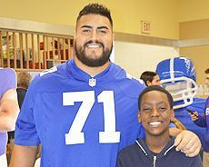 Students with with NY Giant Will Hernandez