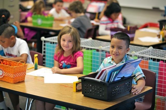 kids smiling at camera at desks